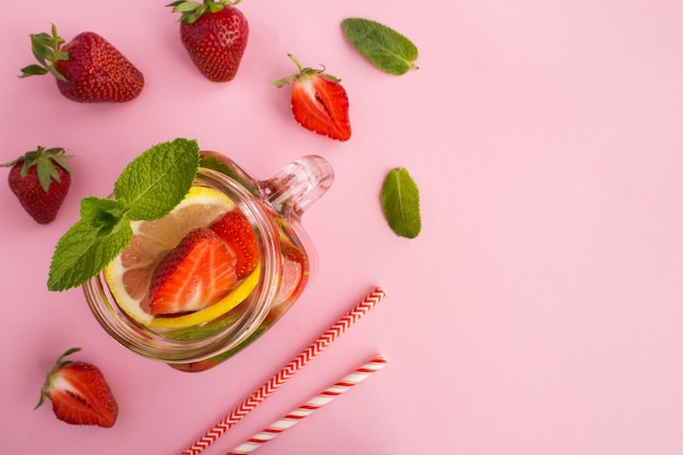 Top view of infused water with strawberry and lemon in the glass