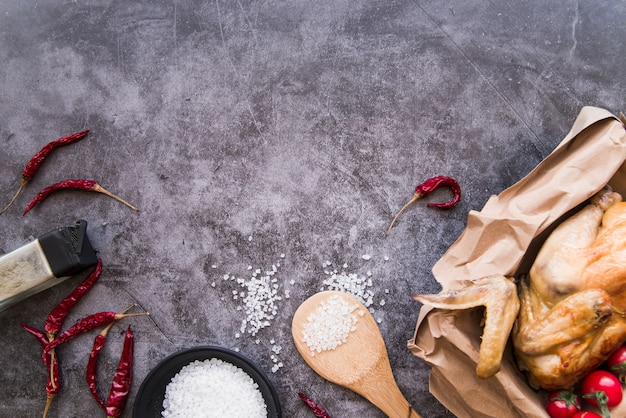 Top view of ingredients and baked chicken over concrete background