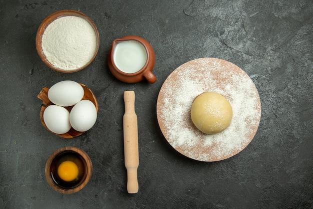 Vista dall'alto ingredienti per pasta uova latte farina sullo spazio grigio