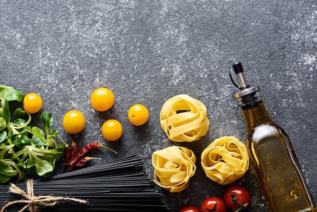 夕食のトップビューの材料-黒いスパゲッティ、フェットチーネ、トマト、コーンサラダ、コピースペースのある灰色の背景にオリーブオイル