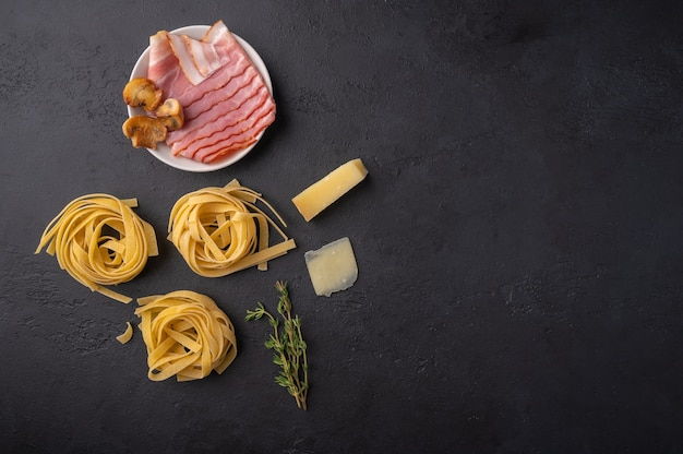 キノコ、ベーコン、パルメザンチーズのパスタフェットチーネのトップビューの材料