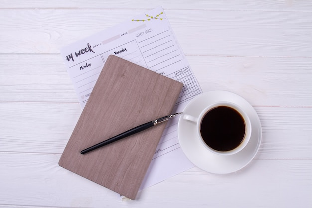 Top view ink pen with diary and cup of coffee.