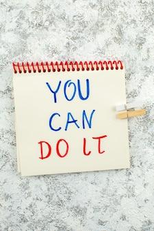 Вид сверху вдохновляющее предложение, вы можете сделать это, написанное в блокноте на белом сером фоне