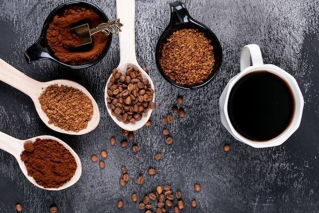 Вид сверху растворимого кофе в деревянных ложках и кофейная чашка на темной поверхности