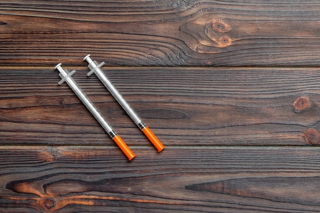 Top view of insulin syringe prepared for injection at wooden background