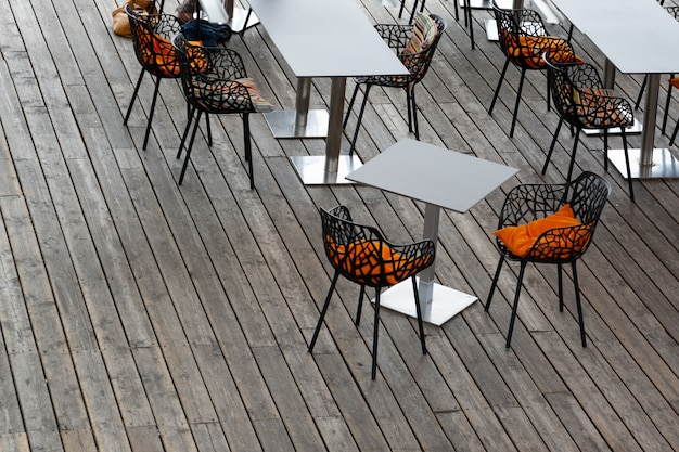 Top view of the interior of the cafe with openwork chairs, bright pillows and gray tables.