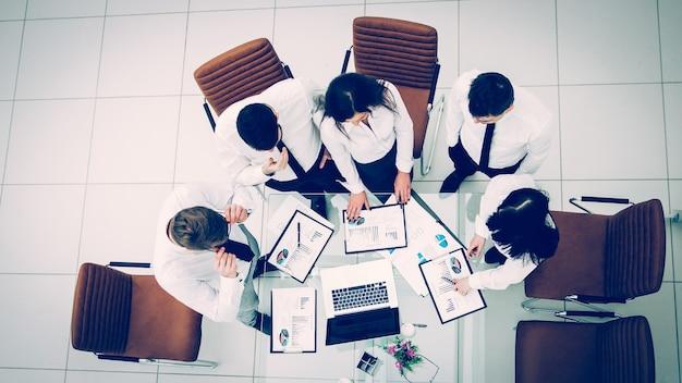 上面図は、現代のオフィスの職場で会社の新しい財務戦略を開発しているプロのビジネスチームです。写真にはテキスト用の空きスペースがあります