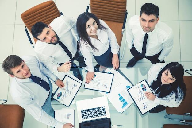 Top view는 현대적인 사무실의 작업 위치에서 회사의 새로운 재무 전략을 개발하는 전문 비즈니스 팀입니다.