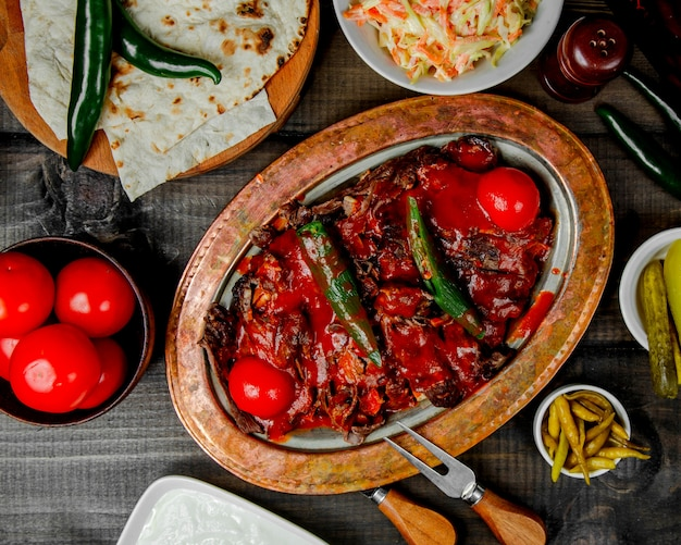Top view of iskender kebab topped with pepper and tomato