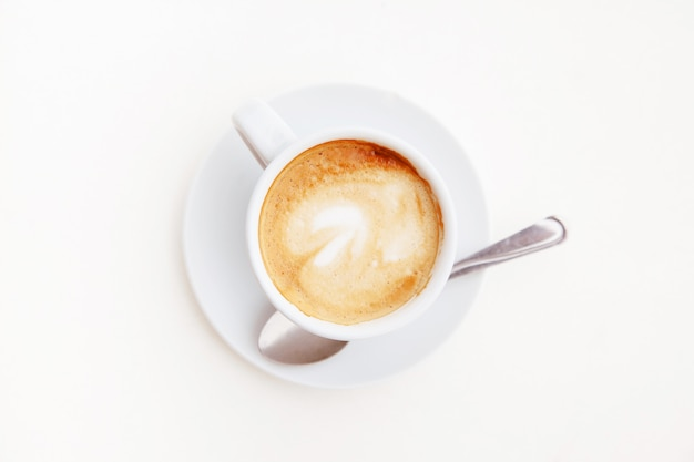 Top view of isolated cup of coffee on white table. hot cappuccino with foam at home.