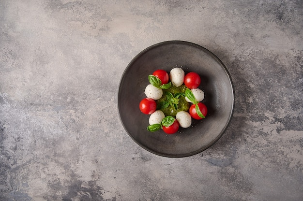 Top view italian caprese salad with ripe tomatoes fresh basil and mozzarella cheese in black plate