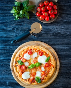 Top view of italian classic pizza margherita over a wooden table with toppings