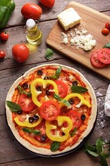 Вид сверху итальянской домашней пиццы, нарезанной с начинкой из паприки с ингредиентами на деревянном столе