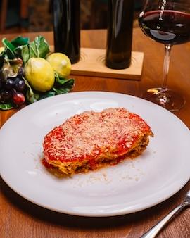Vista dall'alto di lasagne italiane guarnite con salsa di pomodoro e parmigiano grattugiato