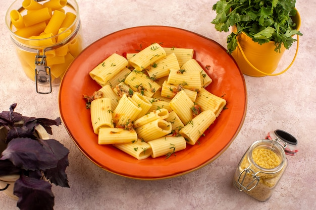 A top view italian pasta cooked tasty salted inside round orange plate with flower and raw pasta on pink desk