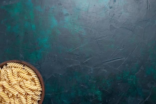 Вид сверху вкусной итальянской пасты, выглядящей внутри коричневого горшка на темно-синем столе, итальянская паста, еда, ужин, приготовление теста