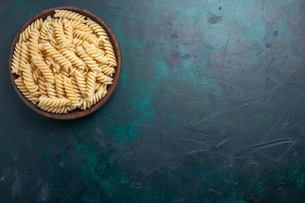 上面図イタリアンパスタ紺色の机の上の茶色の鍋の中を見ておいしいイタリアンパスタ料理食事ディナー調理キッチン生地
