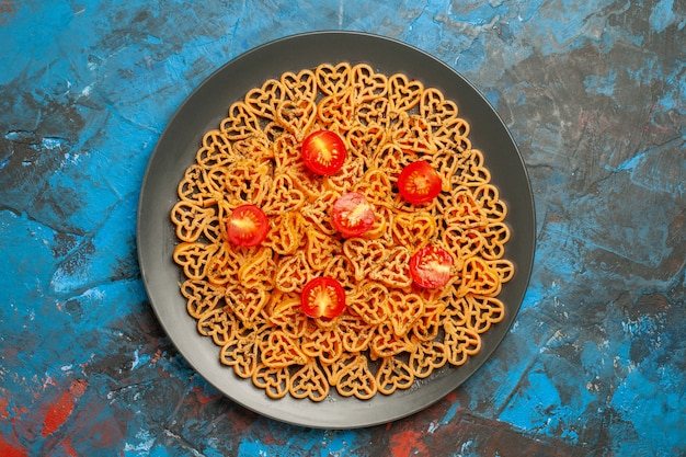 Top view italian pasta hearts cut cherry tomatoes on black oval plate on blue table