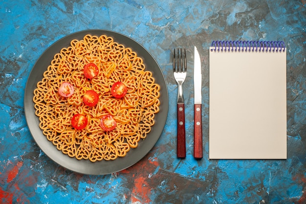 Top view italian pasta hearts cut cherry tomatoes on black oval plate fork and knife notepad on blue table