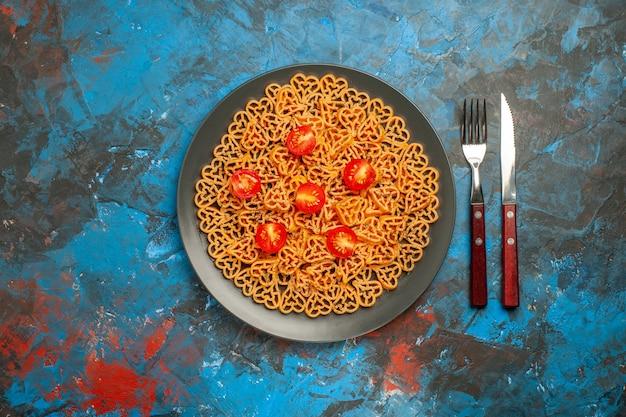 上面図イタリアンパスタハートは、黒い楕円形のプレートフォークにチェリートマトをカットし、青いテーブルのコピー場所にナイフをカットします