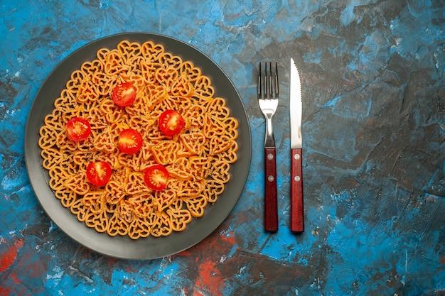 上面図イタリアンパスタハートは、黒い楕円形のプレートフォークと青いテーブルの空きスペースにナイフでチェリートマトをカットしました