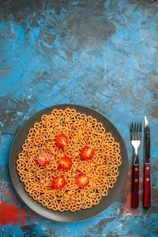上面図イタリアンパスタハートは、黒い楕円形のプレートフォークにチェリートマトをカットし、空きスペースのある青いテーブルにナイフを切ります