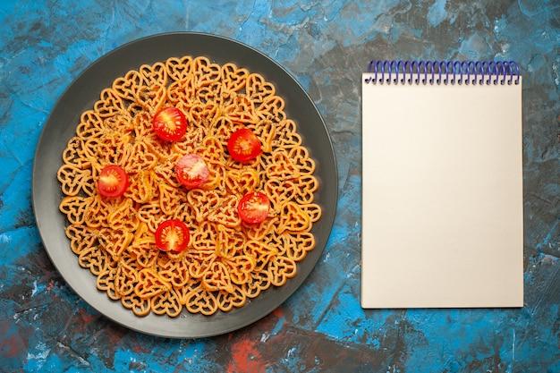 上面図イタリアのパスタハートは青いテーブルの上の黒い楕円形のプレートのメモ帳にチェリートマトをカットしました