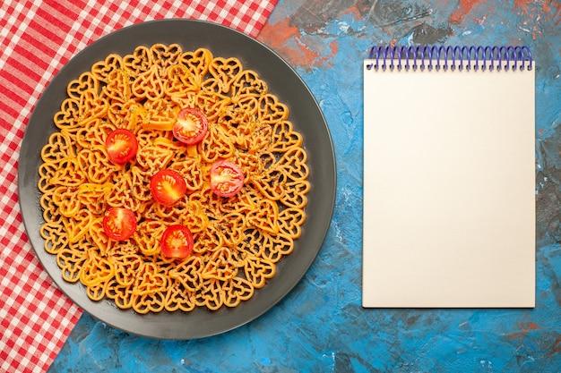 上面図イタリアのパスタハートは、青いテーブルの上の赤白の市松模様のテーブルクロスのメモ帳の楕円形のプレートにチェリートマトをカットしました
