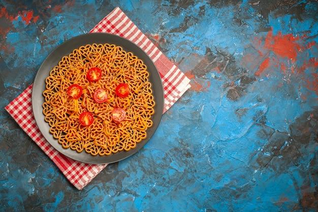 上面図イタリアンパスタハートは、空きスペースのある青いテーブルの上の赤白の市松模様のキッチンタオルのプレートにチェリートマトをカットしました