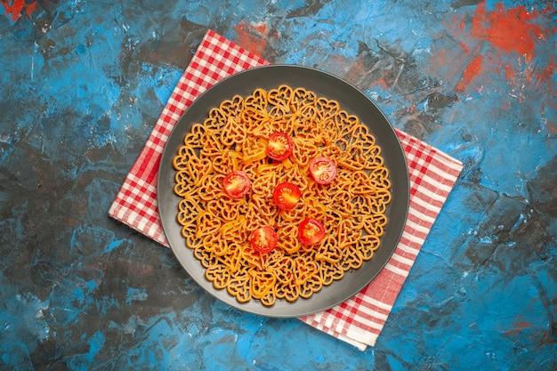 上面図イタリアンパスタハートは青いテーブルの上の赤白の市松模様のキッチンタオルのプレートにチェリートマトをカットしました