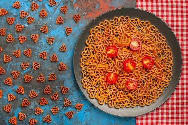 上面図イタリアのパスタハートは、赤い白い市松模様のテーブルクロスのプレートにチェリートマトをカットし、青いテーブルに赤いハートのパスタを散らばった