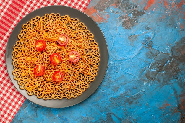 Top view italian pasta hearts cut cherry tomatoes on oval plate on red white checkered tablecloth on blue table with free space