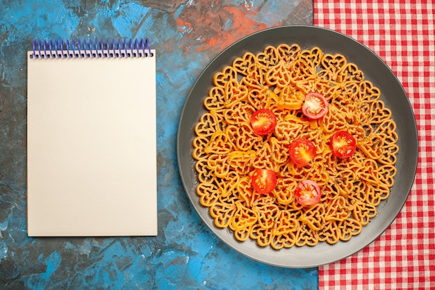 Top view italian pasta hearts cut cherry tomatoes on oval plate on red white checkered tablecloth notebook on blue table