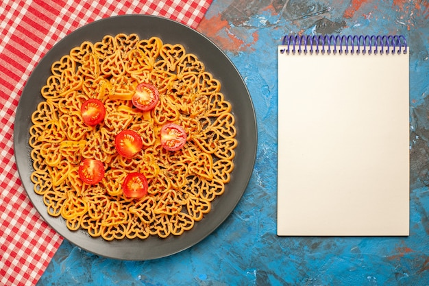 Top view italian pasta hearts cut cherry tomatoes on oval plate on red white checkered tablecloth notepad on blue table