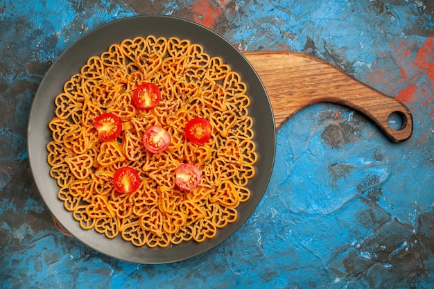 Top view italian pasta hearts cut cherry tomatoes on plate on cutting board on blue table