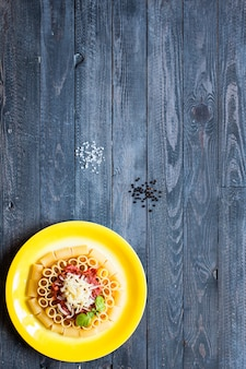 Top view of italian pasta rigatoni with bolognese sauce on a rustic wooden background