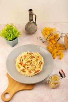 Un pasto gustoso di pasta italiana vista dall'alto con verdure cotte e fettine di carne all'interno della lastra grigia insieme a fiori e pasta cruda sul rosa