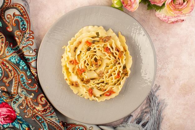 Un pasto gustoso di pasta italiana vista dall'alto con verdure cotte e fettine di carne all'interno della lastra grigia su sciarpa colorata e rosa