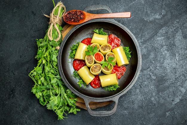 회색 공간에 팬 안에 녹색 토마토 소스와 고기와 함께 상위 뷰 이탈리아 파스타