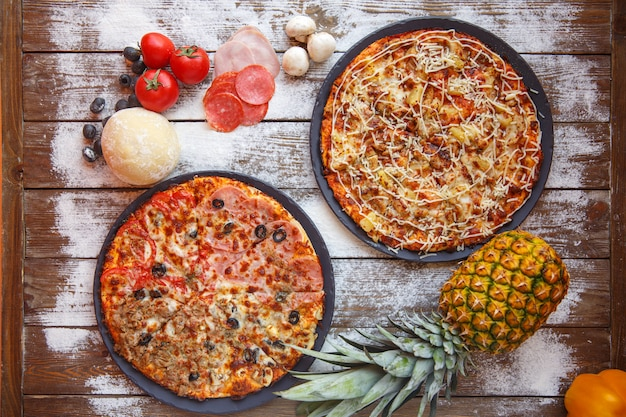 Top view of italian pizzas of four seasons and hawaiian pizzas