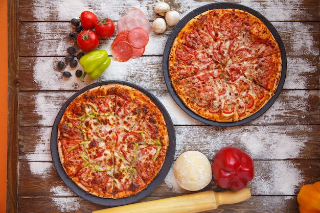 Top view of italian pizzas with tomato sauce, cheese and bell peppers