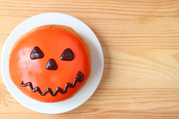 Top view of jack o lantern halloween doughnut served on wooden background