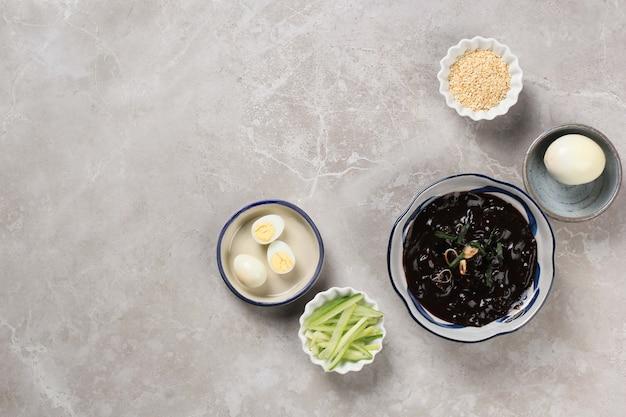 Вид сверху соуса и приправы jajangmyeon. яйцо, огурец и кунжут
