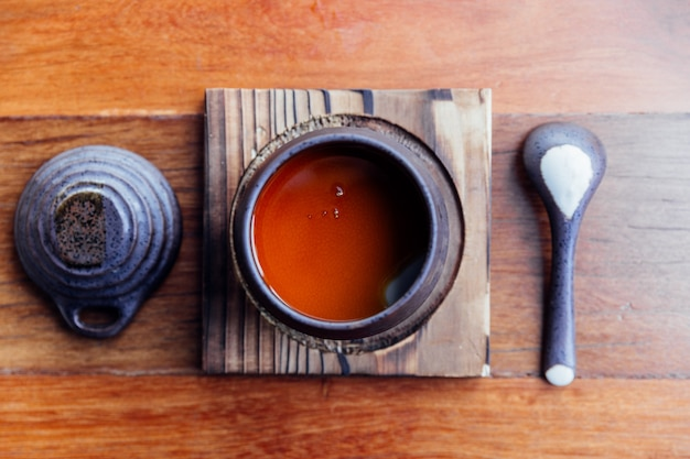 Top view of japanese caramel pudding served in black ceramic cup.