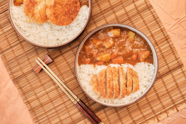 Top view japanese curry rice topping with fried pork and vegetables in white and black plate with chopsticks.