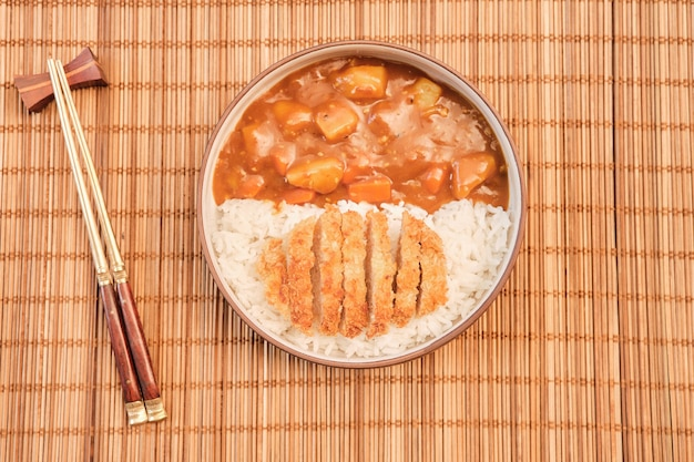 Top view japanese curry rice topping with fried pork and vegetables in white and black