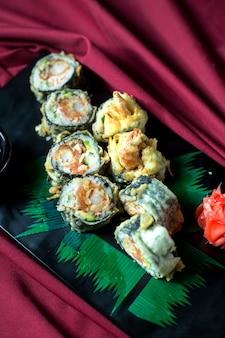 Top view of japanese traditional food tempura sushi maki served with ginger and soy sauce on a black board
