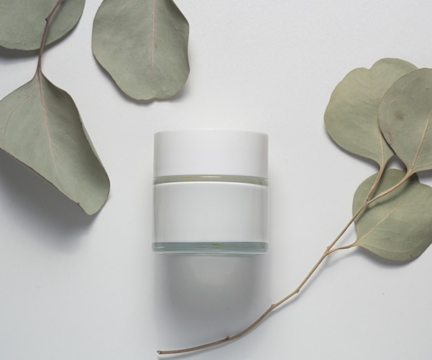 Top view of a jar of cream, with eucalyptus leaves.