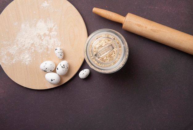 Top view of jar full of oat-flakes and rolling pin with eggs and flour on cutting board on maroon background with copy space