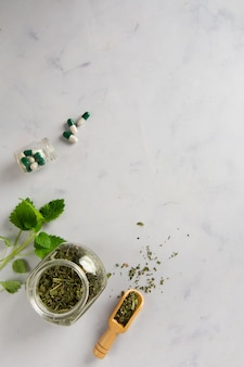 Top view jar with herbs and capsules on the table
